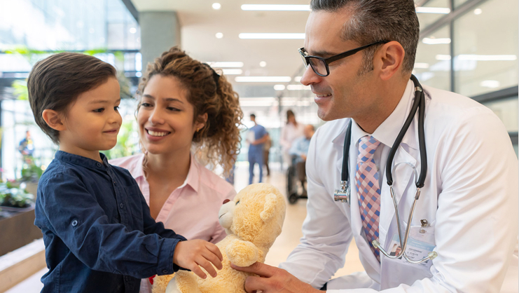 young boy with his mother reaching for teddy bear being given by doctor